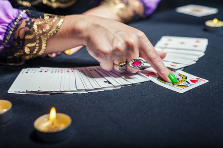 Close up of sorceress telling fortunes using cards