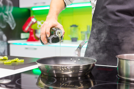 edible: Close up of mans hand pouring oil in the pan