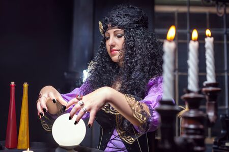 satanism: Sorceress working with crystal ball in her room Stock Photo