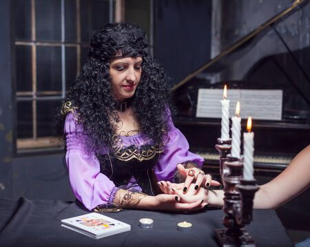 astrologer: Close up of sorceress reading somebodys hand