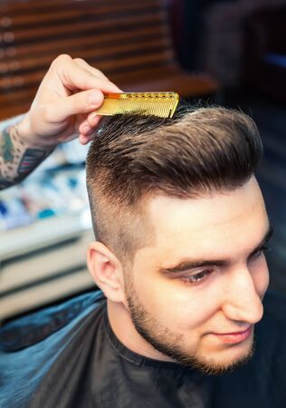 shorten: Cheereful young man having hairdress, barber hands combing out Stock Photo