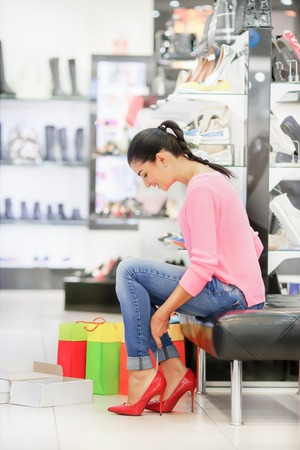 women legs: Young woman fitting red elegant stilettos while shopping Stock Photo