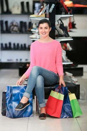 Woman sitting with many shopping bags in the shoe store Stock Photo