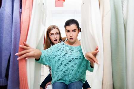 Two excited women looking right in the camera near the stand with pull-overs in the shop Stock Photo