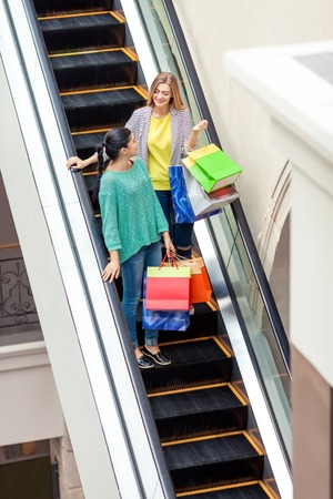 after shopping: Women talks on the moving staircase holding bags after shopping