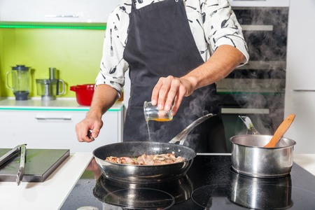 pan: Man cooking meat at home, meat is burning in the pan Stock Photo