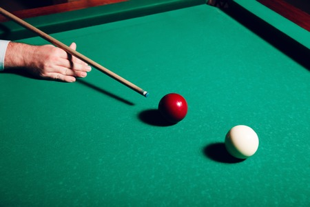 snooker halls: Close up of man preparing to hit while playing billiard