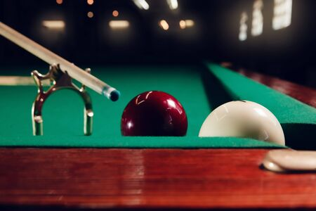 snooker halls: Close up of cue on the stand and billiard balls near the pocket Stock Photo