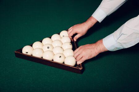 cue sticks: Close up of mans hands preparing billiard balls