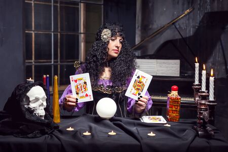 satanism: Sorceress practising witchcraft with cards in her room Stock Photo
