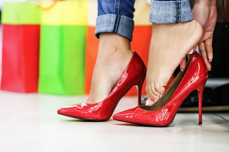 close fitting: Close up of woman fitting red elegant stilettos