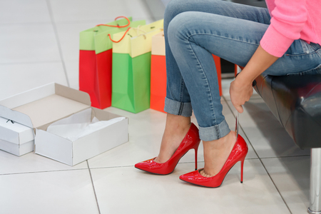 women legs: Close up of woman fitting red elegant stilettos in the shop