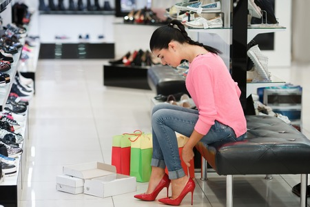 Young woman fitting red elegant stilettos while shopping Stock Photo