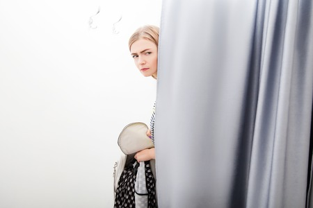 checkroom: Woman trying to steal a dress in the checkroom in the shop Stock Photo