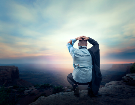 lonely person: Businessman sitting in despair on the edge of the mountain Stock Photo