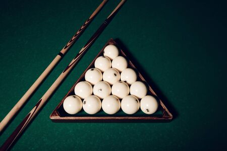 Billiard balls in wooden triangle and pool sticks close up view Stock Photo
