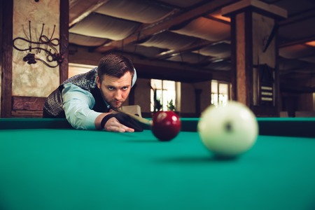snooker halls: Young man concentrating while playing billiard