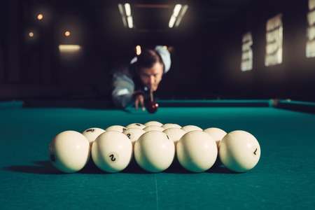 snooker halls: Young man preparing to shoot balls in triangle Stock Photo