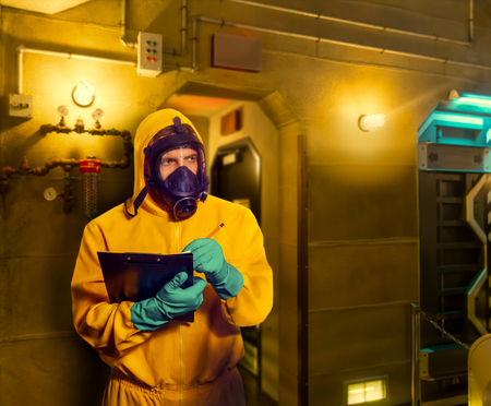 protective suit: Man in protective suit with respiratory mask making notes Stock Photo