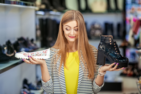 choise: Young woman trying to choose the pair of shoes Stock Photo