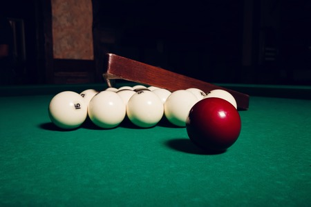Billiard items on the table: balls, stick and triangle