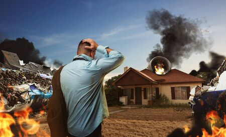 catastrophic: Man is looking at the plane ruins near the house, its burning over there