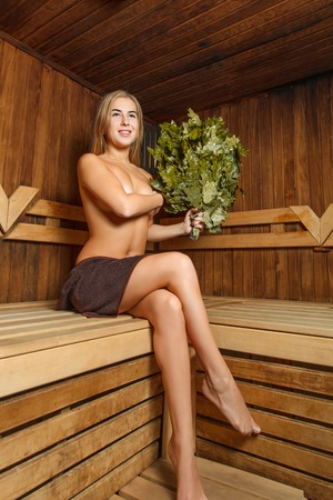 nude girl: Beautiful female in a bathhouse with a broom covers a breast with a hand.