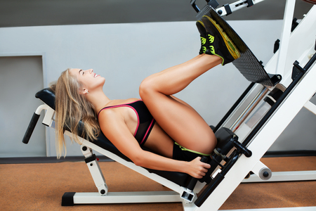 weight machine: Side view of young girl training legs on the sport machine