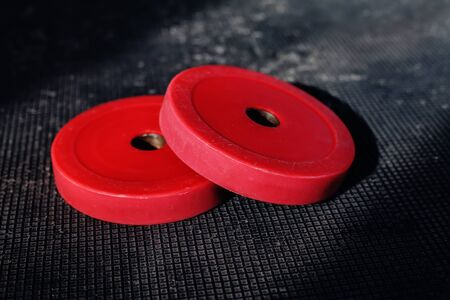 Red weight plates on the floor in the gym