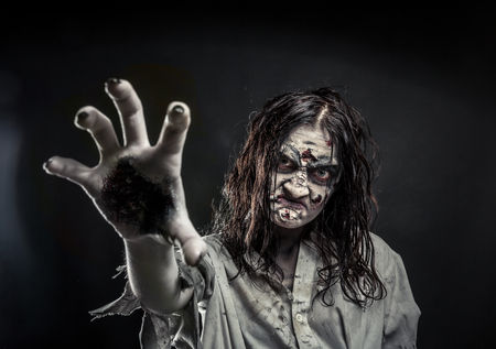 Horror zombie woman with bloody face reaching hand to you Stock Photo