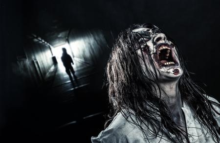 demonio: La chica del zombi gritando de terror en un pasillo oscuro. Víspera de Todos los Santos.