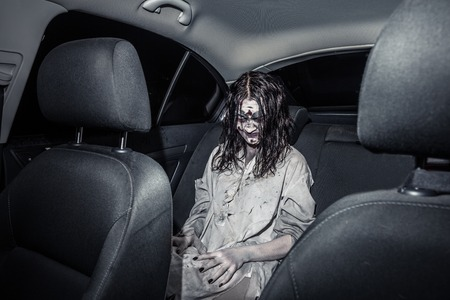 night shirt: The horror zombie woman with bloody face in the car, night city on the background. Scary. Halloween. Stock Photo