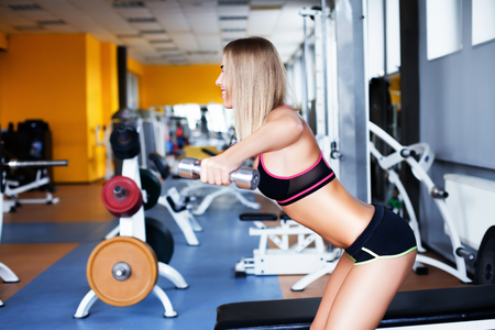 Side view of young girl exercising with dumbbells in the gym