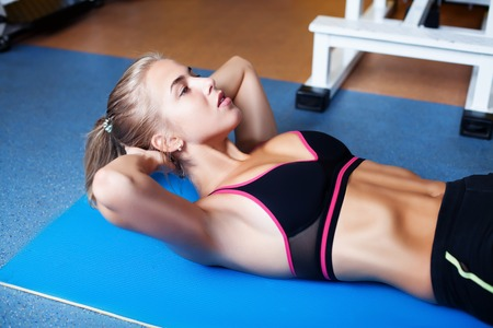 mujeres fitness: Young girl exercising abs in the gym Foto de archivo