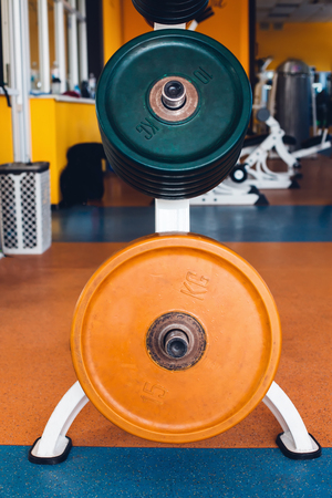 Close up of weight plates on the bar-bells in the gym