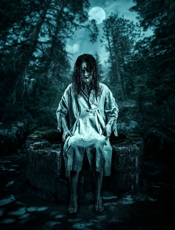 evil girl: Scary corpse sitting on the well in the night forest. Halloween. Stock Photo