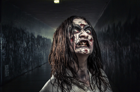 Portrait of the horror zombie woman with bloody face Imagens