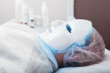 healing process: Woman in the light mask lying on a couch in a beauty salon.