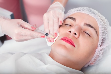 regeneration: Doctor makes an injection syringe in the womans face. Regeneration treatment. Stock Photo