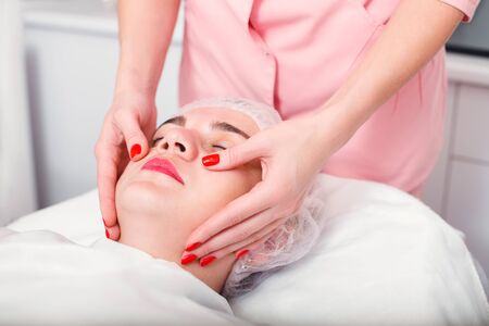 spa therapy: Young woman getting spa treatment at beauty salon. Spa therapy. Face Massage. Facial treatment. Skin and body care.