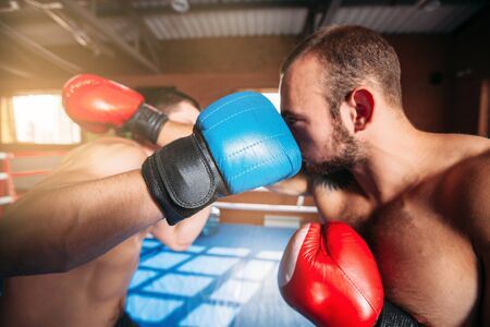 Boxers strike blows to each other. Boxing fighters trainning. Boxing ring on the background. Stock Photo