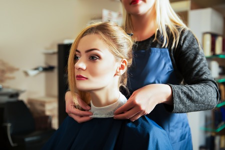 professional woman: Professional hairdresser with beautiful woman in hairdressing salon.