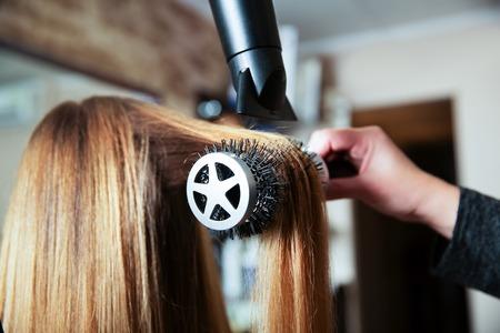 Professionele vrouw kapper maakt kapsel met behulp van föhn voor jonge vrouwen in de schoonheidssalon.