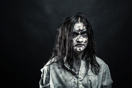 Portrait of the horror zombie woman with bloody face against the black background. Halloween. Scary.