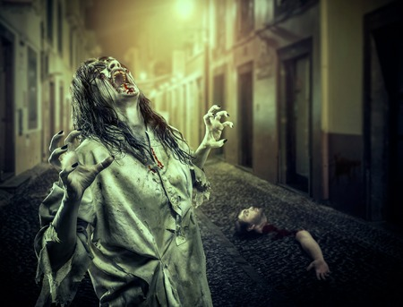 The horror shouting zombie girl on the dark street, bloody hand and head on the background. Vampire. Halloween.