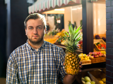 Portrait of smiling man in shirt holds ripe pineapple in hands. Grocery on the background. Stock Photo