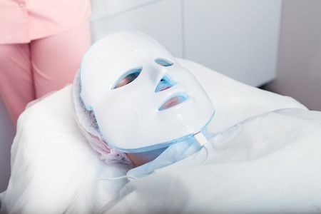 Woman in the light mask lying on a couch in a beauty salon