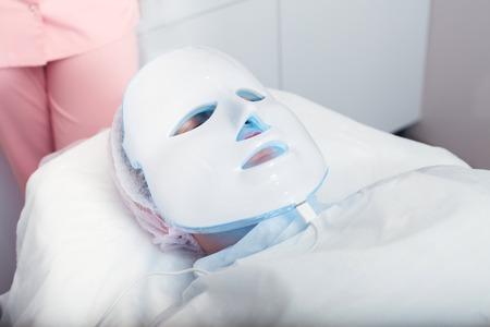 Femme dans le masque de lumière allongé sur un canapé dans un salon de beauté Banque d'images - 66680428
