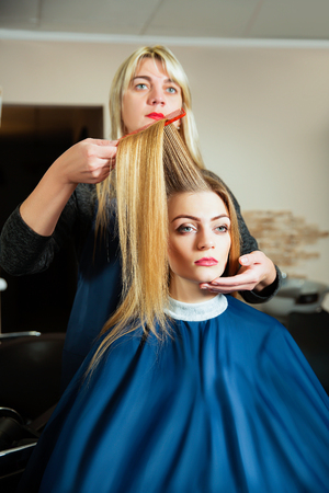 haircutting: Professional hairdresser making hairstyle with hairbrush in hand to young female in hairdressing salon. Stock Photo