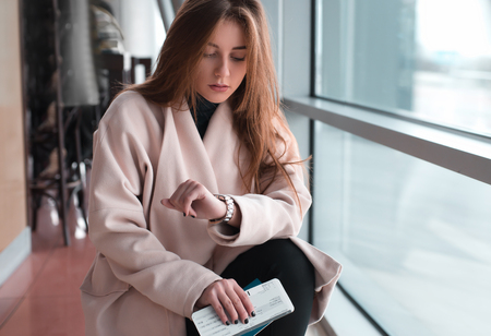 looking at watch: Young woman in international airport, waiting for her flight, checking her wrist watch and looking upset or worried. Arrival, missed, canceled or delayed flight concept.